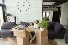 Couple relaxing on couch moving into new home with boxes Royalty Free Stock Photos
