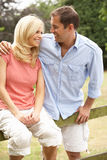 Couple Relaxing In Countryside Sitting On Fence Royalty Free Stock Photos
