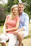 Couple Relaxing In Countryside Sitting On Fence Stock Image