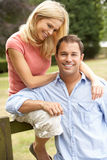 Couple Relaxing In Countryside Sitting On Fence Stock Images