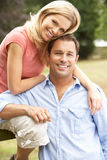 Couple Relaxing In Countryside Sitting On Fence Stock Photo