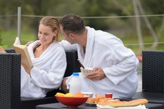 Couple relaxing while eating breakfast outdoors royalty free stock photos