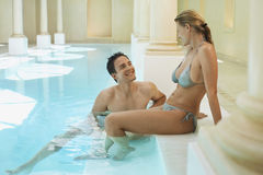 Couple Relaxing At Edge Of Swimming Pool Royalty Free Stock Image