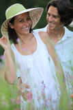 Couple relaxing in field Stock Photography