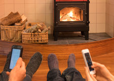 Couple relaxing by fire looking at separate mobile devices. Feet and socks of a couple relaxing by fire in woodburner looking at separate mobile devices - focus Royalty Free Stock Images
