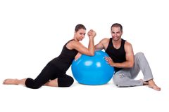 Couple relaxing on fitball. Sportive couple relaxing on fitball in gym isolated on white Royalty Free Stock Photo