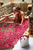 Couple Relaxing In Flower Petal Covered Pool Stock Image