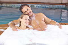 Couple relaxing in foam bath in whirlpool Royalty Free Stock Image
