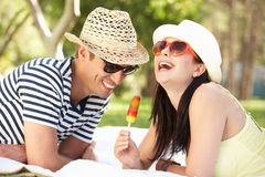 Couple Relaxing In Garden Eating Ice Lolly. Couple Relaxing Together In Garden Eating Ice Lolly Laughing Royalty Free Stock Images