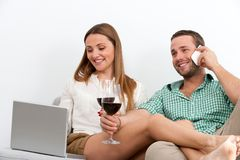 Couple relaxing with glass of wine on couch. Royalty Free Stock Photography