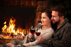 Couple relaxing with glass of wine at fireplace Royalty Free Stock Photos