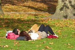 Couple relaxing on grass in autumn park in London Royalty Free Stock Photo