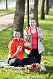 Couple Relaxing on the Grass and Eating Apples Royalty Free Stock Images