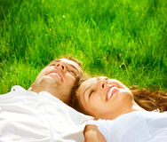 Couple Relaxing on Green Grass. Happy Smiling Couple Relaxing on Green Grass. Park Royalty Free Stock Image