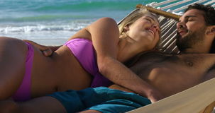 Couple relaxing in hammock stock video footage