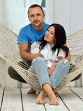 Couple relaxing in hammock smiling, sitting at home Stock Photo