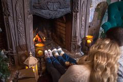 Couple relaxing at home drinking cocoa. Feet in wool socks near fireplace. Winter holiday concept. Couple relaxing at home. Feet in wool socks near fireplace royalty free stock photos