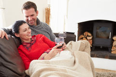Couple Relaxing At Home Drinking Wine Stock Image