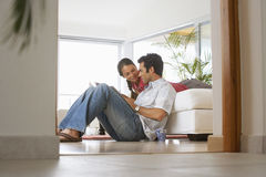 Couple relaxing at home, man sitting on floor, woman on sofa, surface level, view through doorway Royalty Free Stock Images