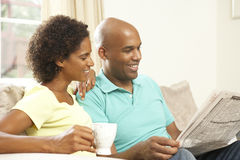 Couple Relaxing At Home With Newspaper Stock Images