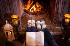 Couple relaxing at home reading a book. Feet in wool socks near fireplace. Winter holiday concept Royalty Free Stock Photos