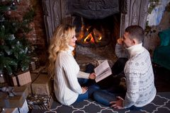 Couple relaxing at home reading a book. Feet in wool socks near fireplace. Winter holiday concept. Couple relaxing at home. Feet in wool socks near fireplace royalty free stock images