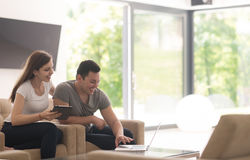 Couple relaxing at  home with tablet and laptop computers Stock Images