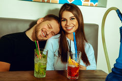Couple relaxing at the hookah bar with cocktails stock photos
