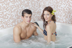 Couple relaxing in the hot tub Royalty Free Stock Photos