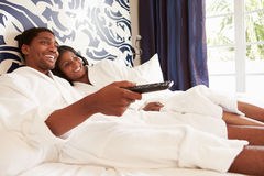 Couple Relaxing In Hotel Room Watching Television Royalty Free Stock Image