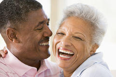 Couple relaxing indoors laughing Royalty Free Stock Photo