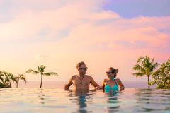 Couple relaxing in infinity pool of exotic luxury resort royalty free stock photography