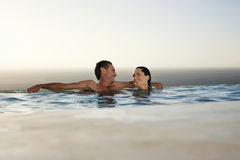 Couple Relaxing In Infinity Pool At Resort Stock Image