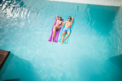 Couple relaxing on inflatable raft at swimming pool. High angle view of couple relaxing on inflatable raft at swimming pool Stock Images