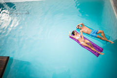 Couple relaxing on inflatable raft at swimming pool. High angle view of couple relaxing on inflatable raft at swimming pool Royalty Free Stock Photo