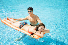 Couple relaxing on inflatable raft at swimming pool. Young couple relaxing on inflatable raft at swimming pool Royalty Free Stock Photos