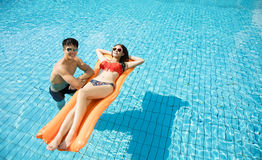Couple relaxing on inflatable raft. Young couple relaxing on inflatable raft at swimming pool Stock Photos