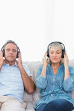 Couple relaxing and listening to music on the couch Stock Photos