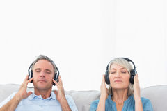 Couple relaxing and listening to music on the sofa Stock Photos