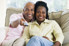 Couple relaxing in living room holding remote Stock Photos