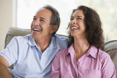 Couple relaxing in living room and laughing Royalty Free Stock Images
