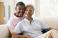 Couple relaxing in living room and smiling Stock Image