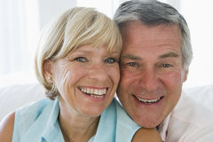 Couple relaxing in living room smiling Stock Photography