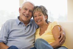 Couple relaxing in living room smiling Royalty Free Stock Image
