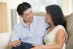 Couple relaxing in living room talking and smiling Royalty Free Stock Photography