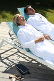 Couple relaxing on long chairs Royalty Free Stock Images