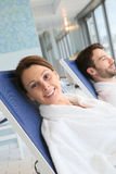 Couple relaxing on long chairs in the spa Stock Photos