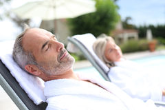 Couple relaxing in long chairs on sunny day Stock Photography