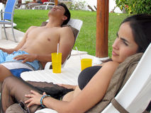 Couple relaxing in lounge chairs Stock Photography