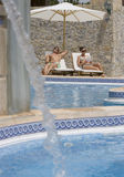 Couple relaxing in lounge chairs at poolside with fountain in foreground Stock Photography